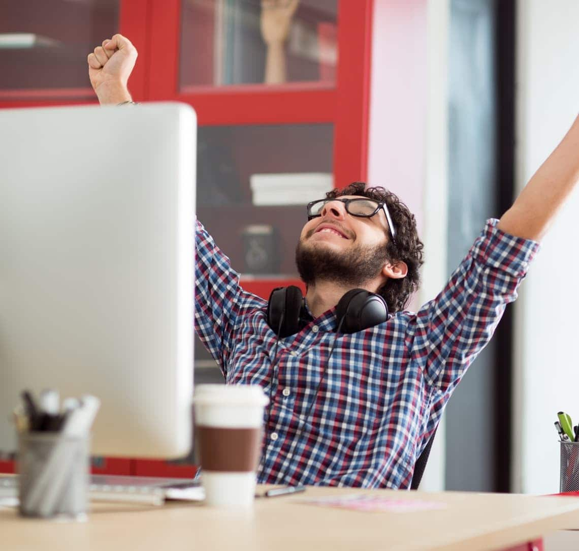 Man happy with hands in the air at computer
