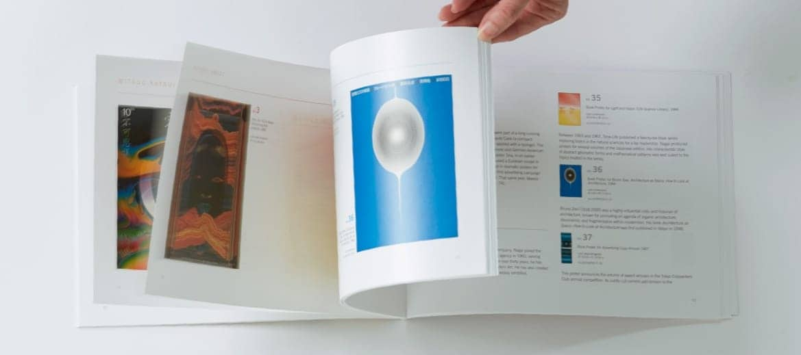 A hand flipping through a design book