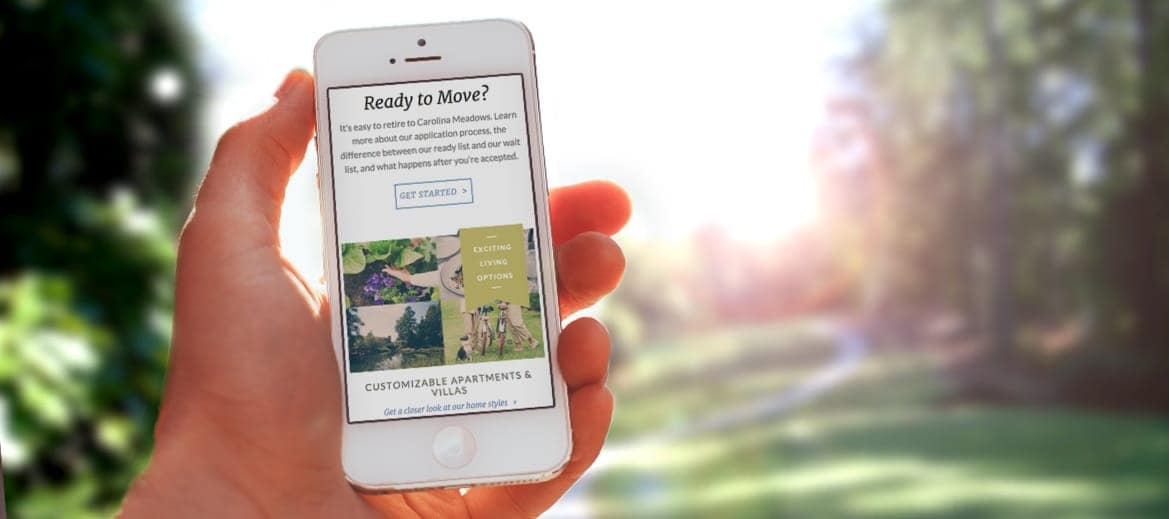 A hand holding a mobile phone showing the Carolina Meadows website