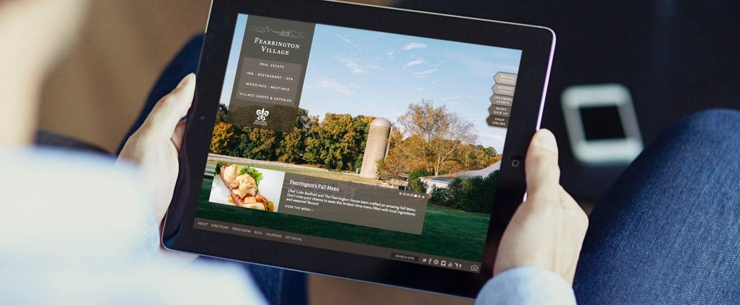 Person holding a tablet device showing the Fearrington Village website