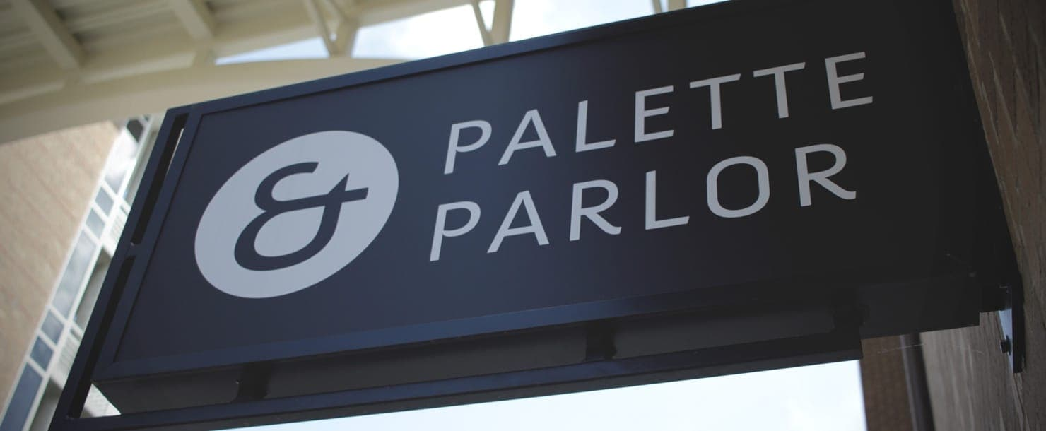 Hero image of a sign showing the Palette & Parlor logo