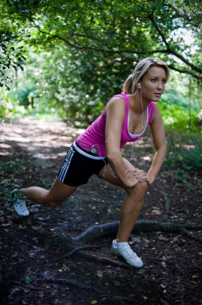 woman stretching on a nature trail