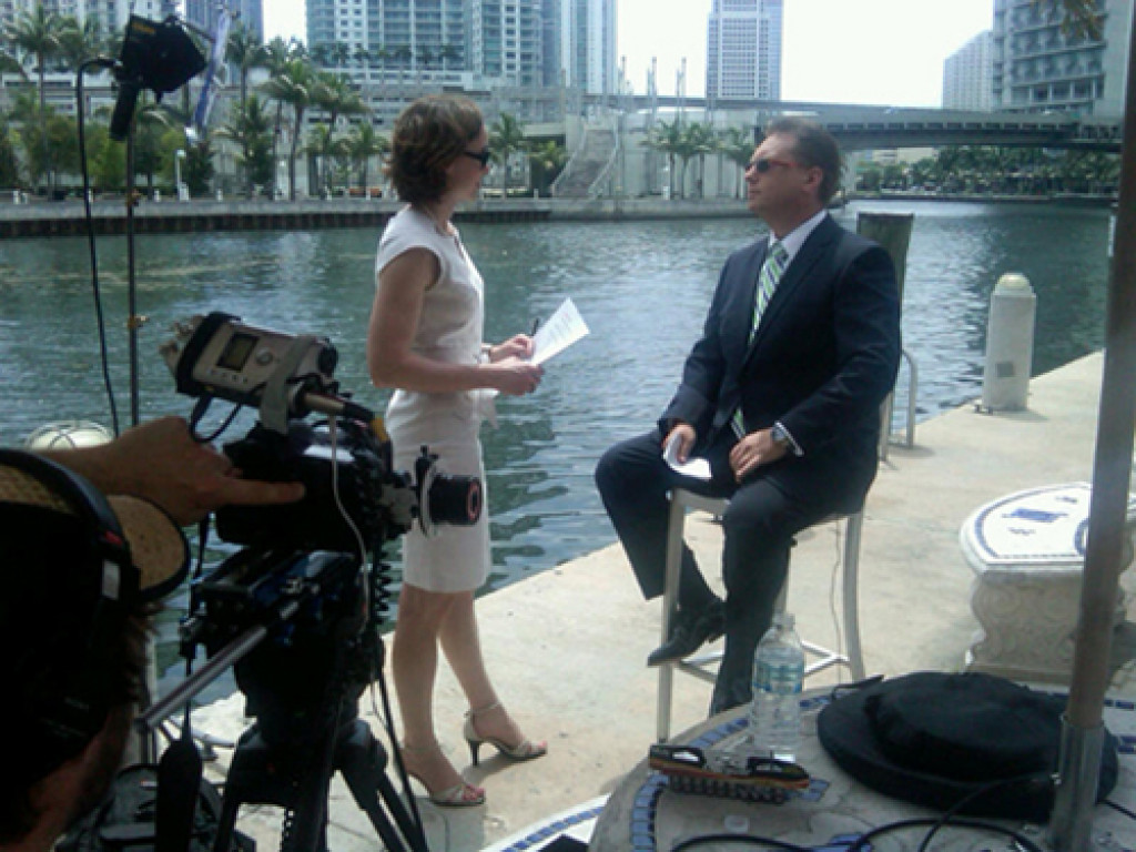 man being interviewed along river in miami