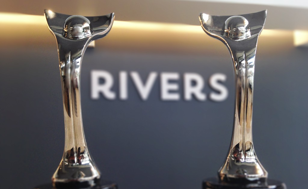 rivers logo between two davey award trophies